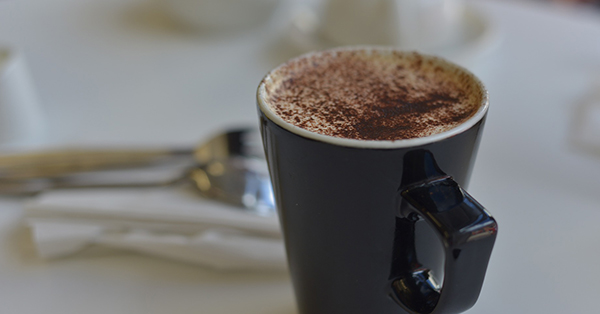 Image description: An angular black mug of hot chocolate dusted with chocolate powder sits on a white table cloth with blurry white napkins and silverware in the background