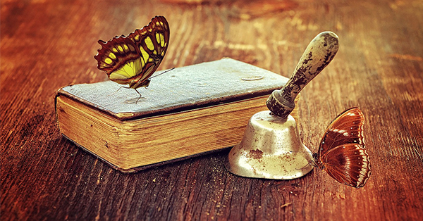 The image is intended to be symbolic of the magic of fairy tales. An old book and old bell sit on a rough wooden surface. Perched on the book is a yellow and brown butterfly and perched on the bell is a brown and white butterfly.