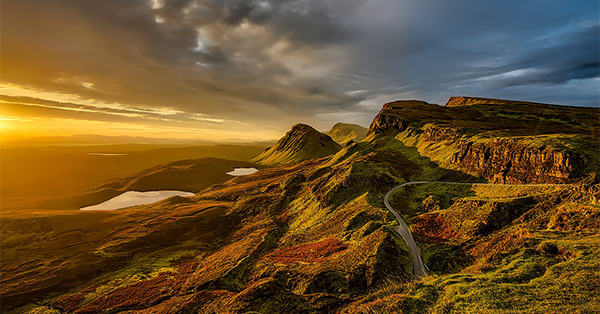 This image is meant to capture the feeling of an exciting adventure. A road traverses a rocky, mountainous landscape that is dramatically lit by the setting sun.