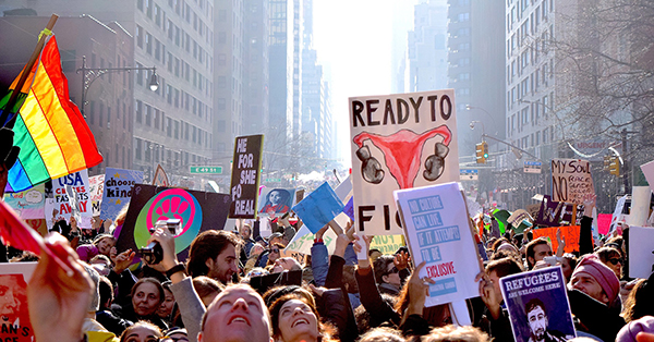 "Photograph of the Women's March showing a street between tall gray buildings packed with people with signs. There is a rainbow flag backlit by the sun, a large sign depicting a uterus with boxing gloves, a poster saying ""Refugees are welcome here,"" and many other only partially legible signs."