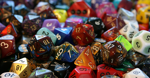 This is an image of a pile of multicolored dice. These are the types of dice used to play tabletop role-playing games. The pile include 20-sided, 12-sided, 10-sided, 8-side, 6-side, and 4-sided dice. Many of the dice are metallic and have different colors artistically swirled together.