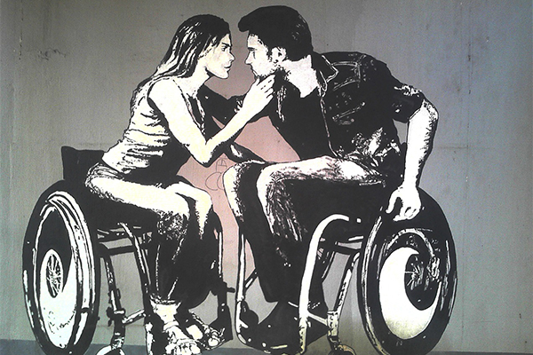 This is a photograph of graffiti on a wall. The graffiti is a black and white artwork of two people who appear to be a white cisgender woman and a white cisgender man, both of whom are in wheelchairs with artistic designs on their wheels. They are leaning toward each other and touching while gazing into each other's eyes in an intense, romantic fashion.