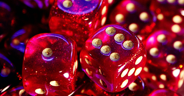 This is a photograph of a pile of dramatically lit, hot pink, six-sided dice with a blue light reflecting off of them