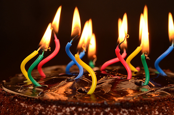 Photograph of a round chocolate cake with glossy frosting and a group of lit pink, yellow, green, and blue spiral shaped birthday candles burning on top.