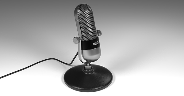 Photograph of a silver and black desktop microphone sitting on a white surface with its black cord trailing off to the left.