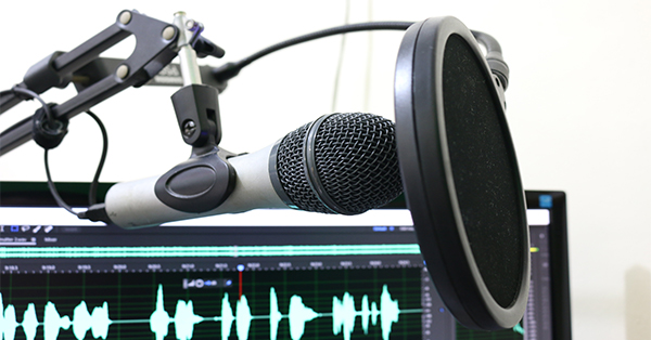Photograph of a microphone being held up in a stand with a pop filter in front of it. In the background is the top of a computer screen displaying an audio editing program.