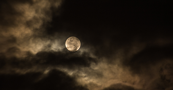 Photograph of the full moon illuminating wispy clouds which are curling around the moon dramatically.