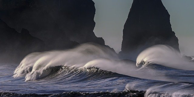 Photograph of waves on a windy day. The sun is illuminating the water as the wind blows the spray from the cresting waves into dramatic flowing tails. These flowing arches of spray contrast dramatically with the dark rocky cliffs behind them. Underneath the water is deep blue.