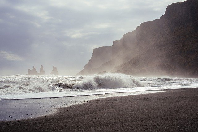 Photograph of the afternoon sun reflecting silver off rough waves on a dark beach. To the right a steep dark cliff with a rippling edge lead out toward a cluster of steep jagged islands. The air is luminous with wisps of mist and fog that hang suspended as they slowly rise up to the silver clouds above.